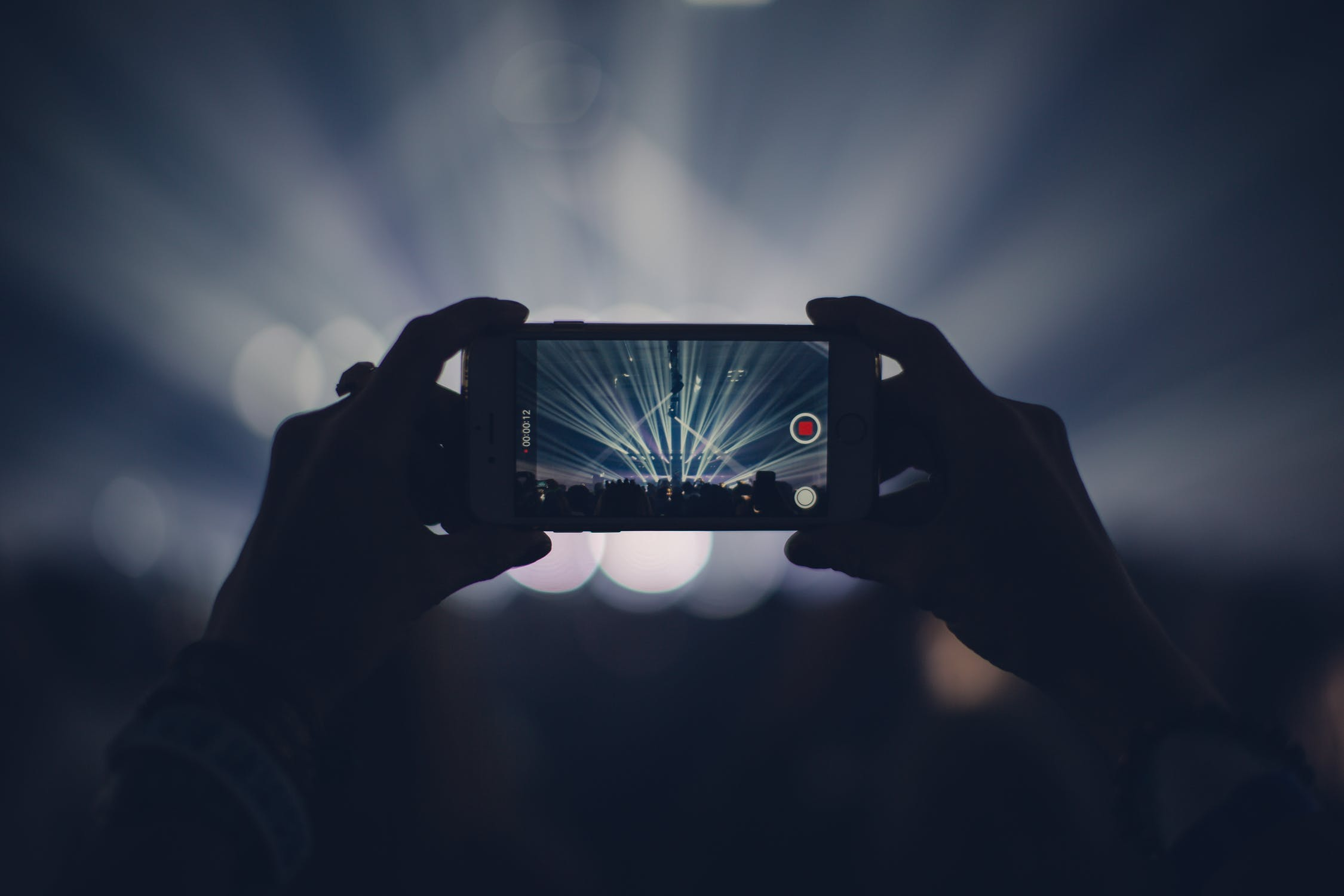 taking a video on phone at concert