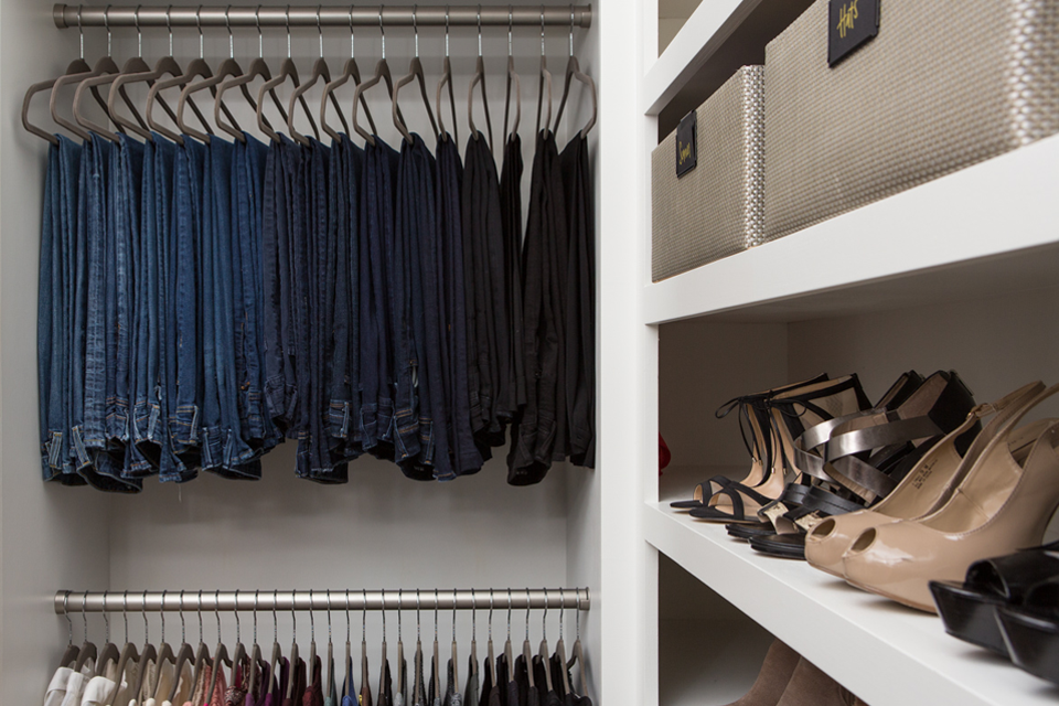organized master closet with clothes and heels