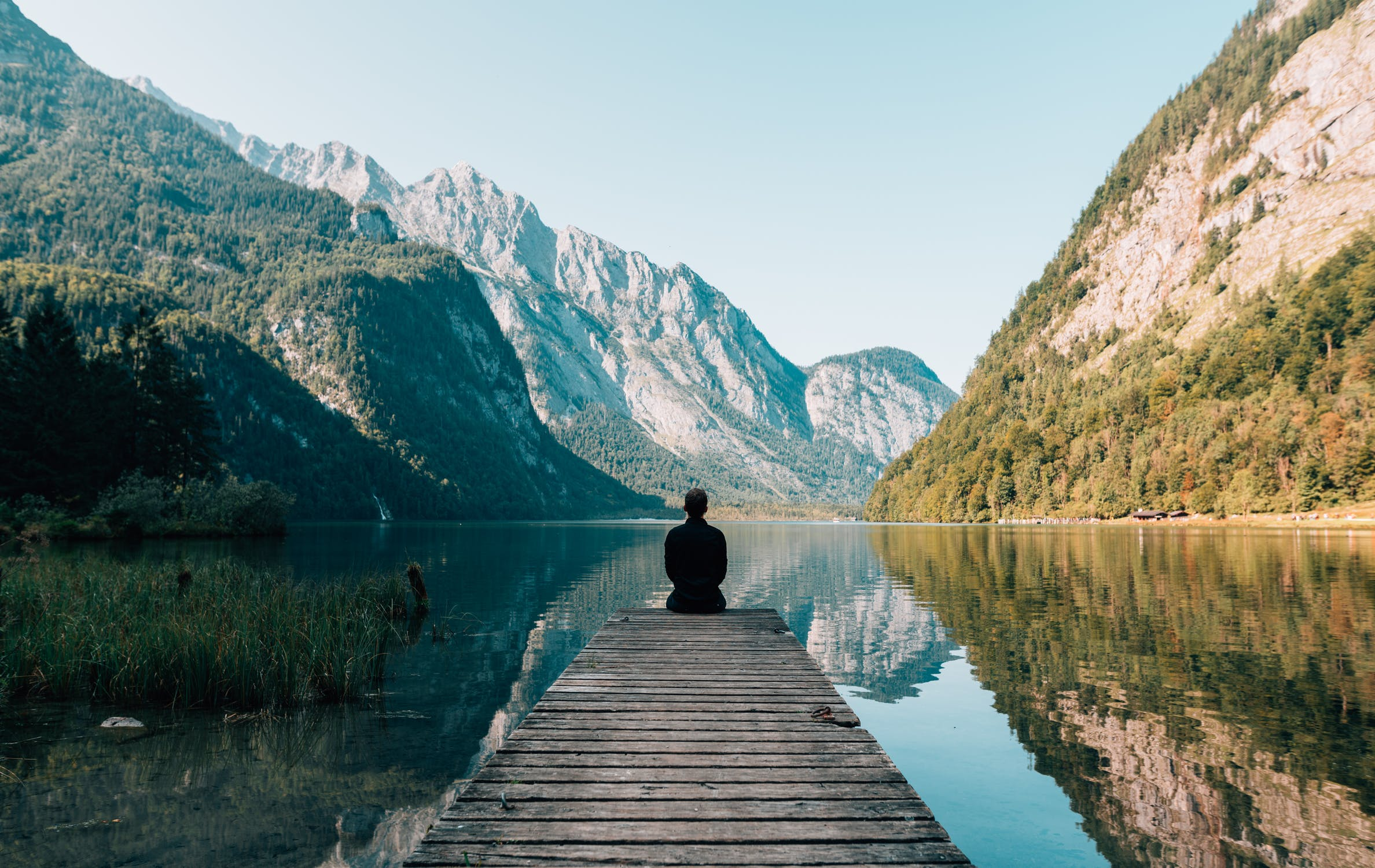 man sitting at the end of a doc on a lake reflecting on his life