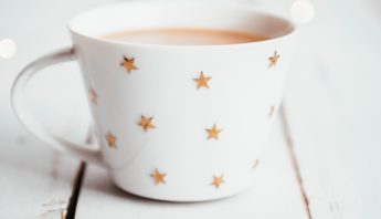 soothing cup of tea in star mug on white table